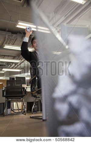 Businessman preparing to throw paper into wastebasket
