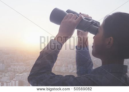 Double exposure of young businesswoman holding binoculars over cityscape of Beijing