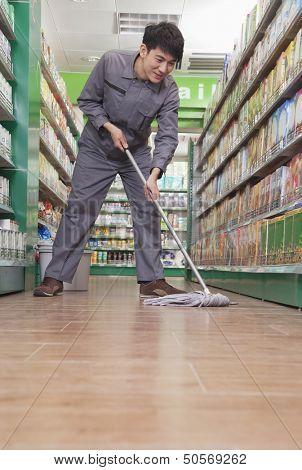 Caretaker Cleaning Floor in Supermarket