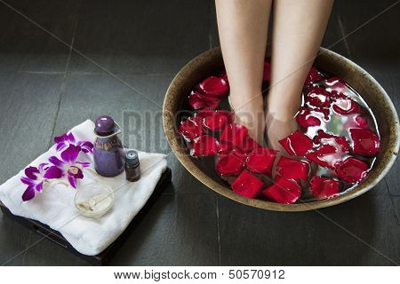 Woman's Feet Soaking in Water with Rose Petals