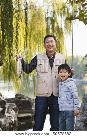 Father and son displaying fishing catch at lake