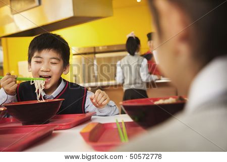 School boy eats noodles in school cafeteria