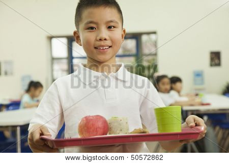 School boy holding food tray in school cafeteria