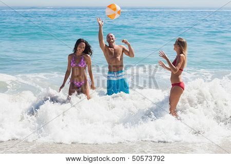 Happy friends playing with a beachball in the sea together