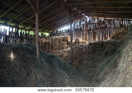 old Barn with the sun streaming from outside and straw and hay on the floor of the hayloft
