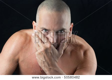 Confident Man Looks To Camera, Shaved Head And Shirtless