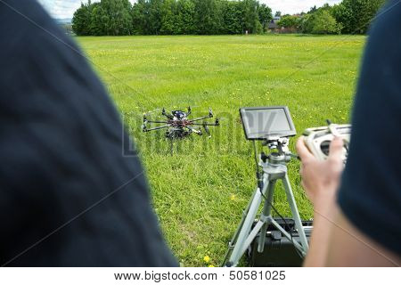 Midsection of young technicians operating UAV helicopter in park