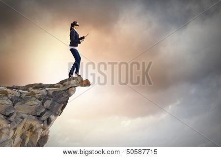 Image of businesswoman in blindfold standing on edge of mountain