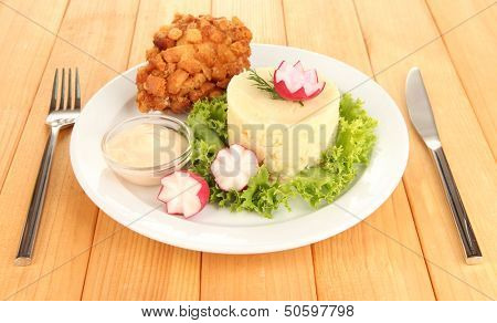 Chicken Kiev on croutons with mashed potatoes, on wooden background