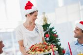 stock photo of christmas meal  - Cheerful woman wearing santa hat and bringing a roast chicken at a christmas dinner - JPG