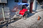 stock photo of rickshaw  - cycle rickshaw on narrow alley in hutong area in Beijing China