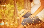 stock photo of expectations  - Pregnant girl sitting in autumnal park - JPG