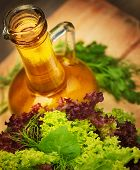 Olive oil and fresh green vegetables on wooden table, tasty salad dressing, lettuce leaves, organic