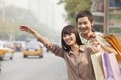 Young couple with shopping bags hailing a taxicab in Beijing