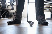 stock photo of miniature golf  - Businessman playing golf in his office - JPG