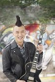 image of half-shaved hairstyle  - Young man with punk Mohawk holding guitar - JPG