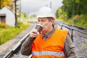 Worker with a coffee on the railway in summer