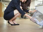Young businesswoman looking through wastepaper bin in office