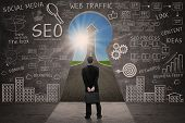 image of keyhole  - Businessman looking through keyhole with success road with SEO business doodle on blackboard