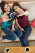 stock photo of selfie  - Two friends on the couch taking a selfie with smartphone at home in the living room - JPG