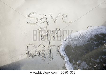 save the date, written in sand and being washed away by wave