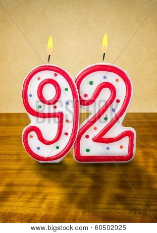 Burning birthday candles number 92 on a wooden background