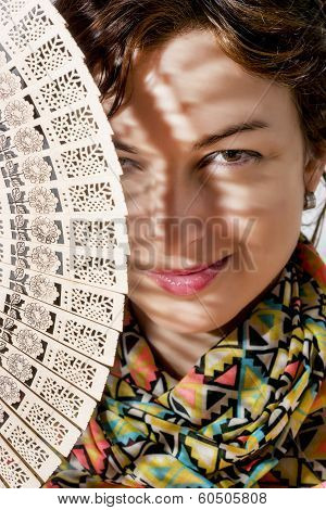 Smiling Woman Peeks Out From Behind Traditional Fan
