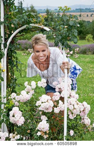 Beautiful Blonde Woman Posing With A Blooming Rose
