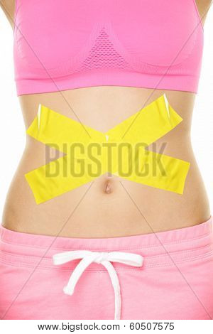 Stomach pain health digestion problems concept with tape crossed over woman belly. Take care of your body, food poisoning or other concept. Conceptual healthy lifestyle image.