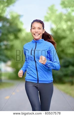 Happy woman runner healthy lifestyle concept with girl jogging smiling training outside in park for marathon. Beautiful mixed race Asian Caucasian female model fresh and vivacious.