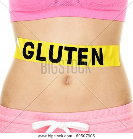 Gluten allergy, health and Celiac disease and digestion concept with GLUTEN text written on stomach sign on woman belly. Conceptual food allergies image.