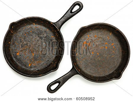 Set of Two Rusty Cast Iron Skillets over white.