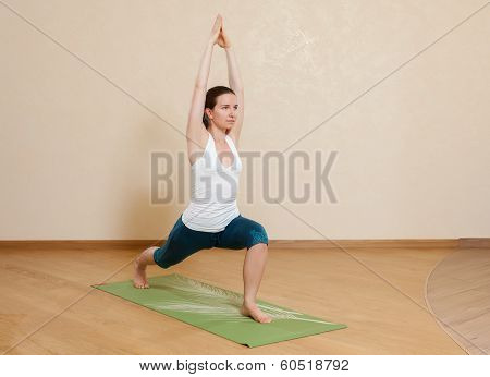 Caucasian Woman Is Practicing Yoga At Studio (virabhadrasana)