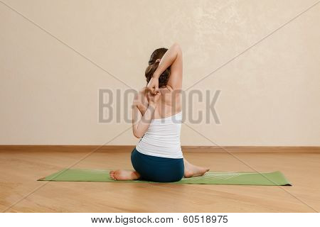 Caucasian Woman Is Practicing Yoga At Studio (gomukhasana)