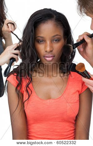 Assistants applying make-up to a female model over white background