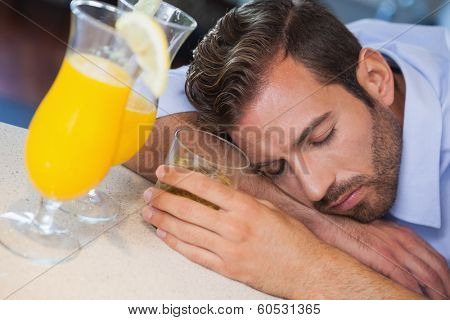Drunk businessman sleeping on bar beside cocktail at the local bar