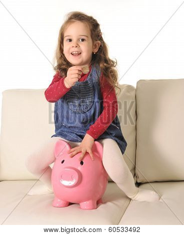 Happy Cute Little Girl Sitting On Huge Piggy Bank Inserting Coin