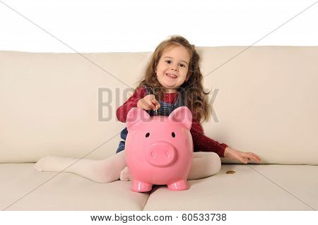 Cute Little Girl Playing Puts Coin In Huge Piggy Bank On Sofa