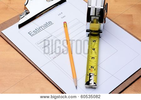 Closeup of a Contractors estimate form with a pencil and tape measure on a wooden table. Horizontal format filling the frame.