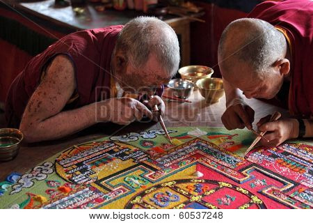 LADAKH, INDIA - SEPTEMBER 03, 2011: Buddhist monks making sand mandala in Diskit gompa at Nubra valley. Mandala - is a spiritual and ritual symbol in Hinduism and Buddhism, representing the Universe.