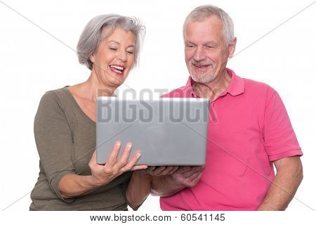 Senior couple with computer in front of white background