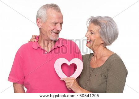 Senior couple with heart in front of white background