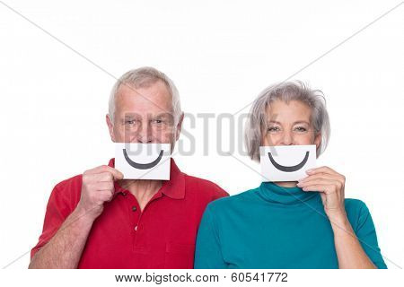 Senior couple with smiley and unhappy sign in front of white background