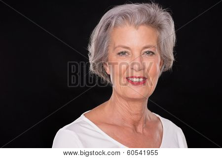 Smiling senior woman in front of black background