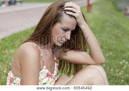 Sad young woman sitting on green grass
