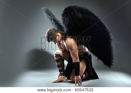 Studio shot of handsome man posing as fallen angel