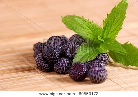Blackberry in a wooden Board slide with fresh spicy greens