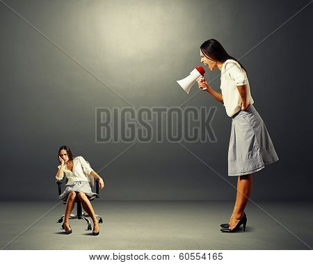 big angry businesswoman screaming at lazy woman over dark background