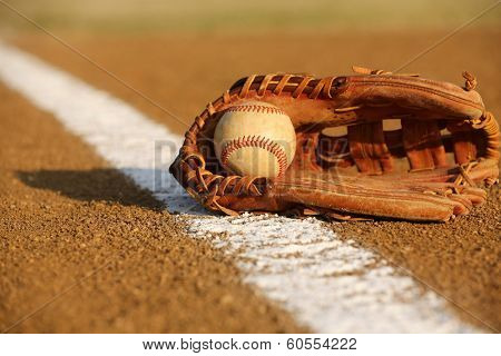 Used Baseball in a Glove in the Infield
