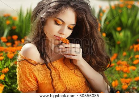 Beautiful Teenage Model Girl Smelling Flower, Over Marigold Flowers Field
